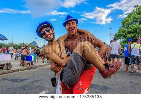 RIO DE JANEIRO, BRAZIL - FEBRUARY 28, 2017: One young man holding another man up in his arms on the background of Sugarloaf Mountain during Bloco Orquestra Voadora at Aterro do Flamengo, Carnaval 2017