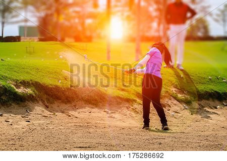 female golf player swinging golf from sand bunker during sunset with flare