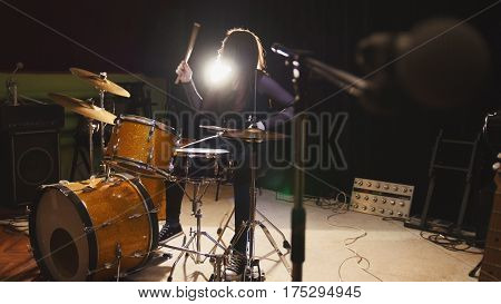 Hard rock music - drum break down performing - attractive girl with flowing hair, backlight