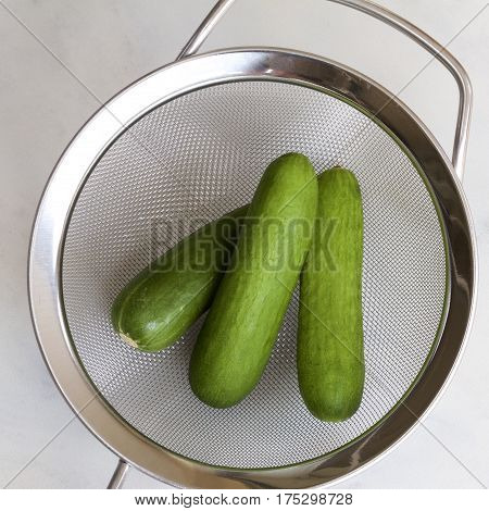 Three small cucumbers in a metal colander.
