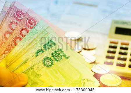 green and red thai banknotes over blur bills and calculator