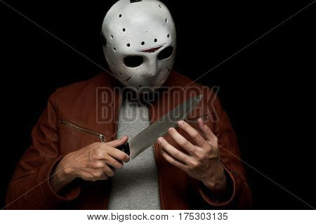 masked murderer in a brown leather jacket holding his knife on isolated black background