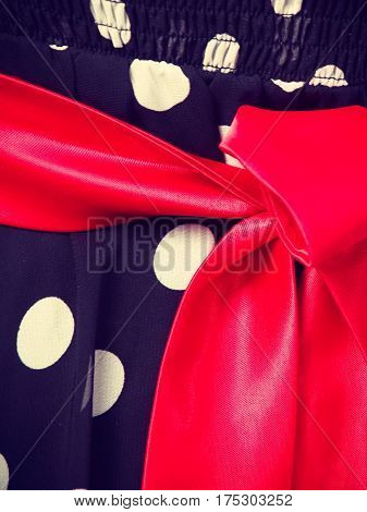 Retro pin up elegant and timeless clothes concept. Close up of retro dotted black dress with big red bow