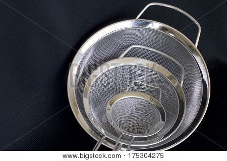 Three metal kitchen colanders together on a black background.