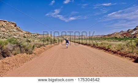 Woman walking on washboard dirt road in deset. Escalante National Monument. Moab. Kanab. Utah. United States.