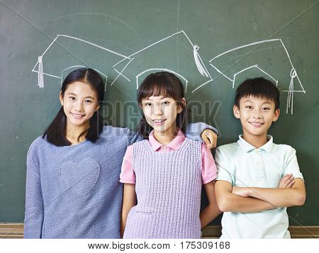 three asian elementary school children standing underneath chalk-drawn doctoral hats in front of blackboard.