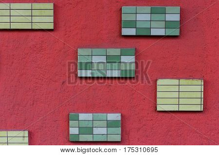 Photo of red wall pasted with green tiles