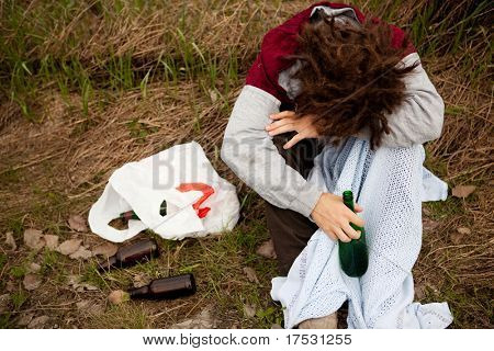 A drunk person sitting in a ditch with a wine bottle