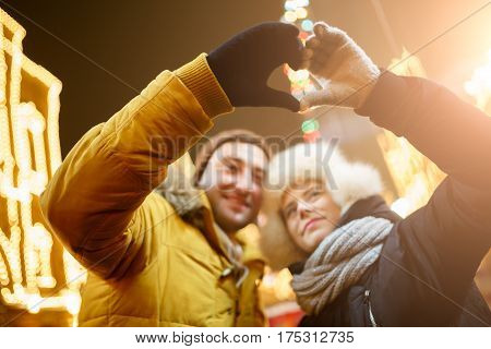 Happy loving couple making from hands heart on street