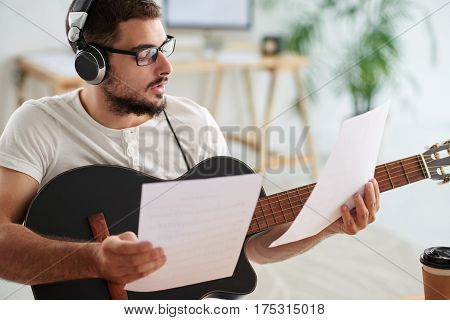 Handsome songwriter in glasses working on new composition