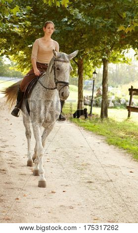 Young female rider riding horse outdoors at autumn.