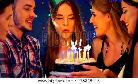 Happy friends birthday celebrating food with celebration cakes. Meet people wear in hat party blow out candles at burning candles. Two women and men have fun in nightclub.Youth celebrates together.