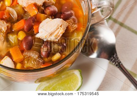 Mexican soup with chicken celery lime bread and vegetables close-up