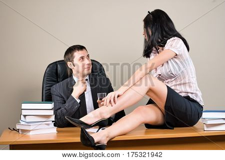 Flirting in the office as a beautiful dark-haired businesswoman pulls a colleague towards her by his tie