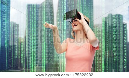 modern technology, cyberspace, entertainment and people concept - happy young woman with virtual reality headset or 3d glasses over city skyscrapers and binary code background