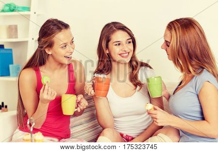 friendship, people, pajama party and communication concept - happy friends or teenage girls drinking tea and eating sweets at home