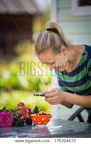 Young smiling woman taking picture of garden berries with her smartphone. Girl making photo of flowers and berries on the table with her telephone. Sending photos of countryside days by telephone.