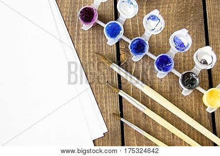 Drawing paint tassels on a wooden table painting Paints in jars