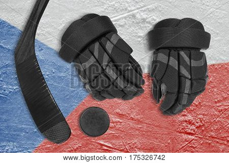 Hockey puck stick gloves and the Czech flag image on the arena ice