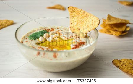 A bowl of creamy hummus with olive oil and chips on light background