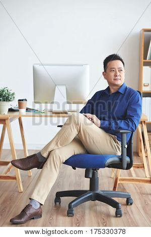 Portrait of Singaporean business executive sitting on chair in his office