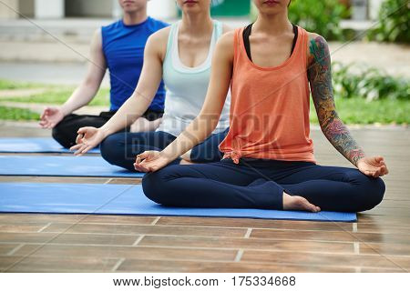 People in lotus position meditating outdoors together