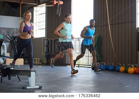 three people racing running sprints in industrial style gym, motion action shot