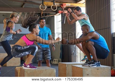 Instructor giving encouragement while fit strong healthy people do box jumps in crossfit gym