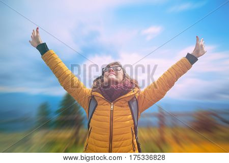 Girl enjoying outdoors with arms wide open.
