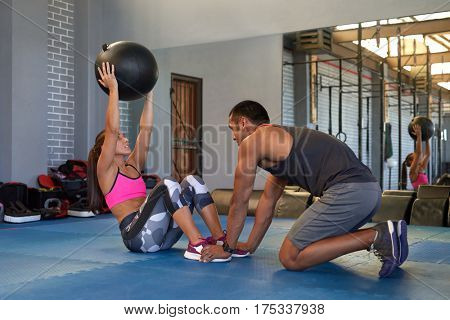 Woman doing med ball exercises in gym with private instructor trainer