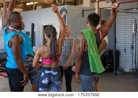 Mixed race trainer bringing everybody in for group cheer positive morale boosting before workout in industrial gym