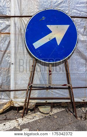 Old mandatory direction sign with scratches and dents in construction site.