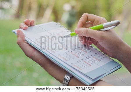 Business holding a calendar Business holding a calendar with nature background Business marking a calendarBusiness marking a calendar