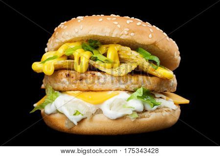A delicious burger isolated on a dark background. Photo causing appetite. The concept of fast food delicious but unwholesome food. Photos can be used to create a menu or advertisement