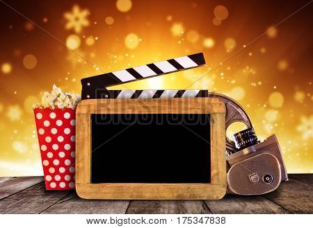 Retro film production accessories placed on wooden planks with blank blackboard for copyspace. Concept of film-making. Shiny abstract background