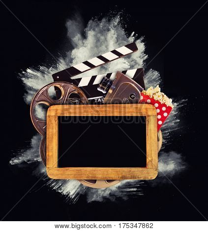 Retro film production accessories with powder explosion on background. Blank blackboard for copyspace. Concept of film-making.