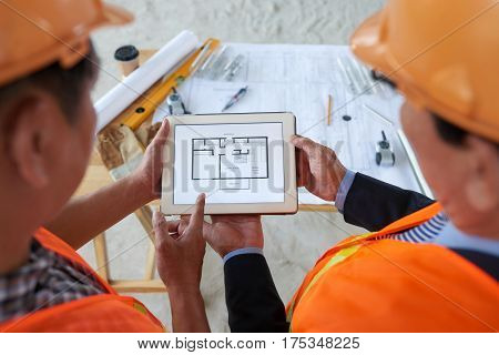 Engineers working with blueprint on tablet computer, view from above