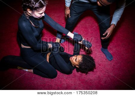 Female fighter dominating her opponent on the ground during MMA battle supervised by a professional referee