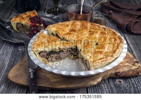Venison Pie with Cranberry Relish as close-up in a backing dish
