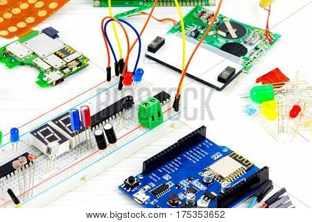 Microcontrollers chips resistors and light-emitting diodes on white desktop of hardware engineer. Engineer workplace