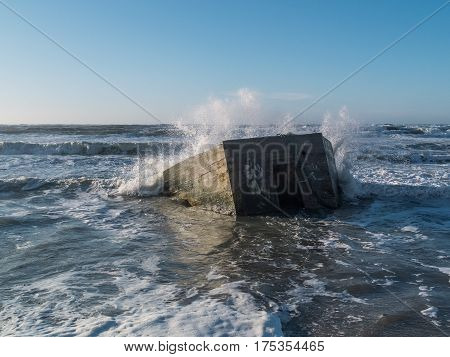 Concrete Bunker on the beach as the water spray from the waves. The bunker is half sunk into the seabed