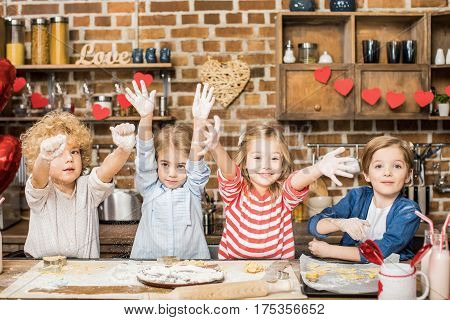 Adorable happy children cooking biscuits and showing hands in flour