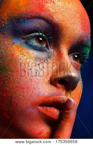 Fashion shooting - portrait of beauty model with colorful powder make up show hush sign on dark studio background. Beautiful woman with creative splash makeup. Abstract colourful art make-up, crop