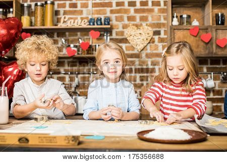Three adorable little children cooking biscuits from unbaked dough