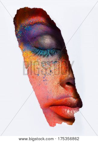 Crop image of female face with eyes closed with colorful powder make up on white background. Beautiful fashion model with creative art makeup. Abstract colourful splash make-up. Holi festival