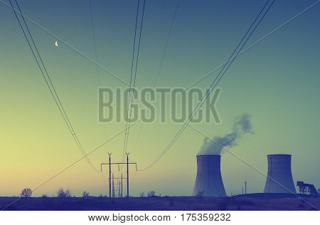Sunset over the nuclear power plant with moon in a sky