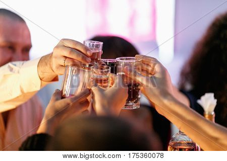 People cheers with wine glasses in the restaurant