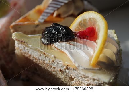 appetizing piece of chocolate cream cake with fresh fruits on top for decoration