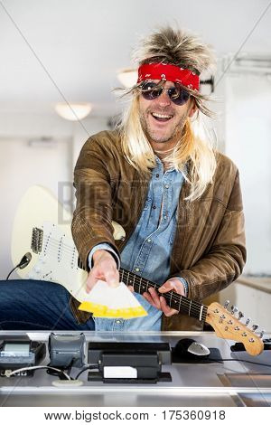 Rockstar with a guitar holding out tickets for his gig in his outstreched arm behind the counter of a ticket booth