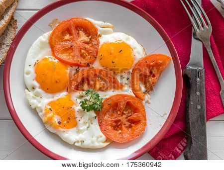 Delicious fried eggs with tomatoes served on white plate with red sides, old tableware, topview
